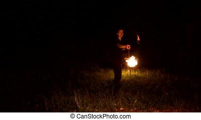 Slow-mo of man in dark rotates burning ball poi. Low key. ...