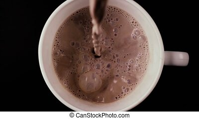 Slow mo. Pour cocoa into the cup, top view