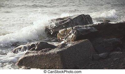 Slow Mo sea surf breaks down on large boulders