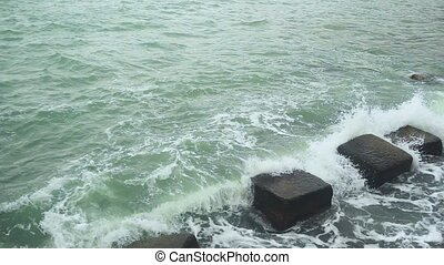 Slow mo the wave breaks against the breakwater stones