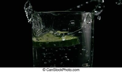 Slow mo. Two slices of cucumber fall into a glass