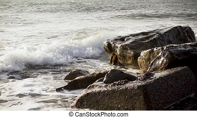 Slow mo wave breaks down on concrete and stones