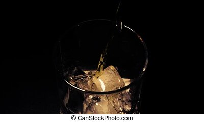 Slow mo whiskey with ice in a glass