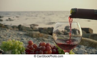 Slow mo wine is poured into a glass on the sea shore