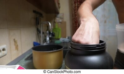 Slow motion. 4k. Young man making a protein shake at home....