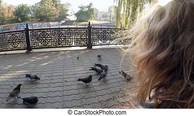 SLOW MOTION. A child in a park feeding pigeons