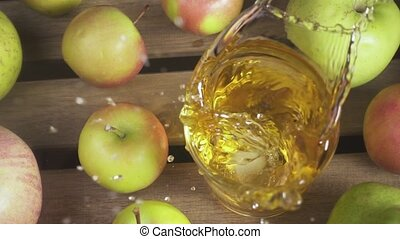 Slow motion a glass of juice on a table among apples top view