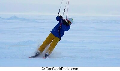 SLOW MOTION: A male athlete is engaged in kiting on skis. He rolls on the ice of a large lake. Rolling, he performs various jumps, coups and other exercises. The snow flies in different directions from the skis. Windy cloudy winter day.