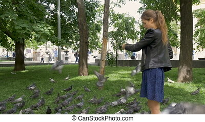 Slow motion A sad beautiful girl is feeding pigeons in the park.