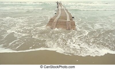 Slow motion a wooden pier in the stormy ocean