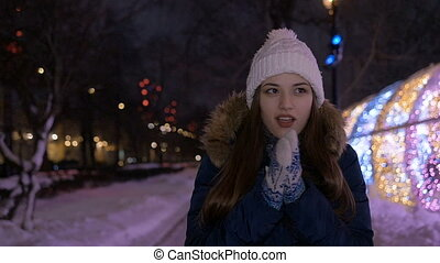 Slow motion. A young girl is waiting for her boyfriend on a date. In the winter in the evening. She froze.