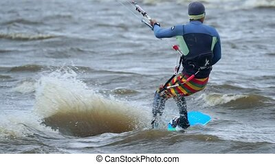 SLOW MOTION: A young man is engaged in kiting. He beautifully skates on the board on the waves of the pond. Strong wind blows. Man loves kiting in extreme weather. Cold autumn weather