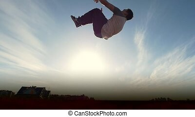 Slow-motion Acrobatics - teenager performing somersault...