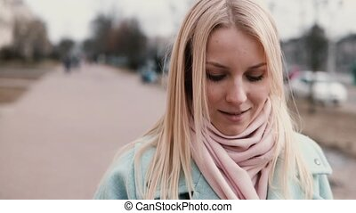 Slow motion adult Caucasian blonde lady texting. Pretty 30s...