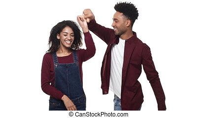 Slow motion African American attractivie young couple enjoy dancing in white studio background.