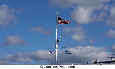 Slow Motion-American Flag Flies in Breeze Above Three...