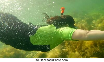SLOW MOTION. An attractive girl swimming underwater