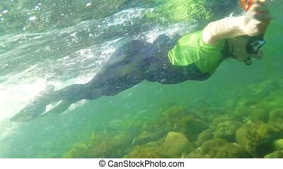 SLOW MOTION. An attractive young girl swimming underwater