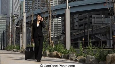 Slow Motion Asian Businesswoman Talking On Telephone Traveling With Baggage?