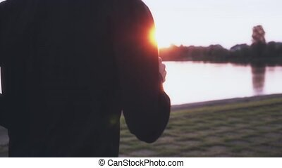 Slow motion athlete reflecting on life jogging. Man in black longsleeve thinking and dreaming to reach goal. Side view.