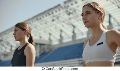 Slow motion: Athlete woman waiting in the starting block on running track