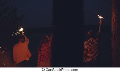 Slow motion back view of young people girls and guys standing in forest holding bengal lights and moving hands on summer night. Nature and fun concept.