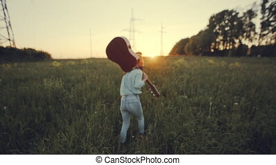 slow motion. beautiful girl playing the guitar in a wheat...