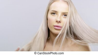 Video portrait of a smiling beautiful young woman touching her long blonde hair. Attractive woman posing over white background. Skincare concept. Hair blowing in the wind in slow motion 6K.