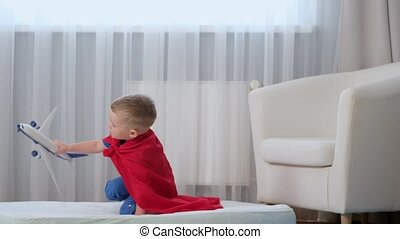 slow motion blond caucasian boy super hero kid playing with toy air plane, jumping on mattress, trampoline with toy in his hands dressed in red raincoat of hero and blue t-shirt in children's room