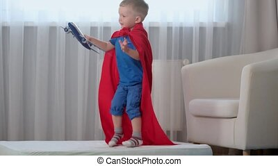 Slow motion blond caucasian boy super hero kid playing with toy air plane, jumping on mattress, trampoline with toy in his hands dressed in red raincoat of hero and blue t-shirt in children's room.