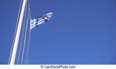 Slow motion blue-and-white flag on flagpole