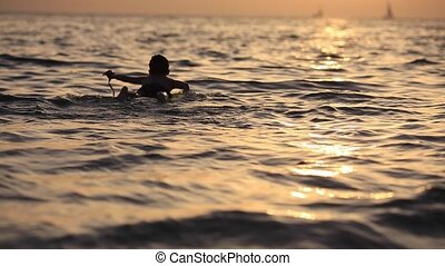 slow motion. boy floating on the sea with a surfboard on the...