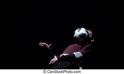 Slow motion, brunet man making tricks with ball on head.