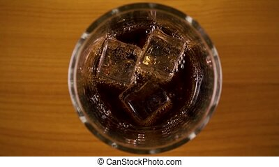 Slow motion. Bubbles in a glass with cola top view