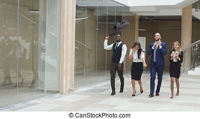 Slow motion. Business people walking along office corridor and celebrate the victory