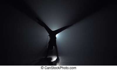 Slow motion. Capoeira. Silhouette of curly girl in darkness...