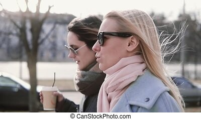 Slow motion caucasian girls walking chatting. Pretty ladies in stylish warm coats and sunglasses talk in the street.