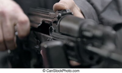 Kalashnikov rifle charging. Close up of charging rifle. Unlocking assault rifle. AK47 loading. Assault rifle ak 47 dual ball detent. Soldier hand charging machine gun