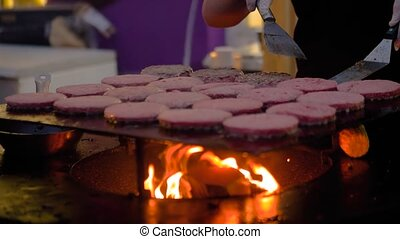 Super slow motion: chef grilling fresh meat cutlets for burgers on brazier with hot flame at summer local food market - close up view. Outdoor cooking, gastronomy, cookery, street food concept
