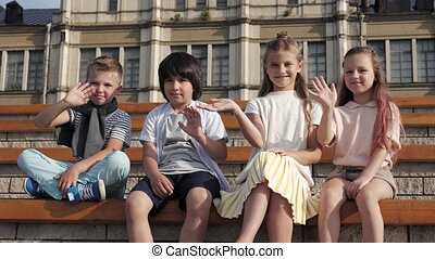 Children smiling and waving hands looking at camera.