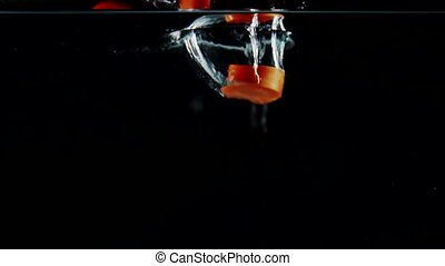 Slow motion chopped carrot falls into water with splashes on black background