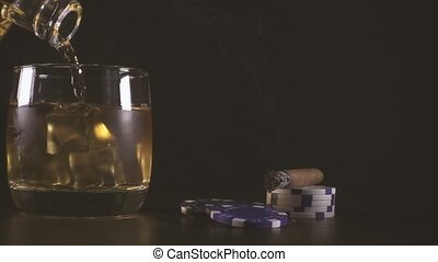 Slow motion cigar and playing chips and a glass of whiskey