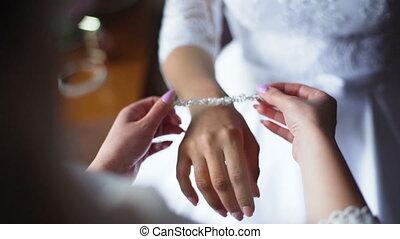 Slow motion. Close-up of bride wearing white diamond...