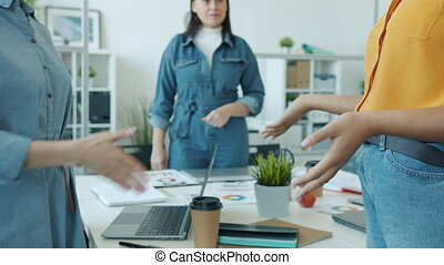 Slow motion close-up of women's handshake expressing agreement in office room while ladies are making deal sorting out differences. People and unity concept.