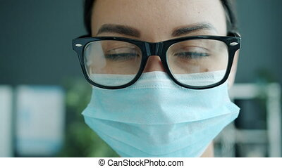 Slow motion close-up portrait of serious lady medic in mask ...