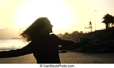 Slow Motion Close up silhouette of Young Woman dancing on a beach with hair blowing in wind looking at sunset over ocean.