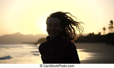 Slow Motion Close up silhouette of Young Woman jogging on a beach with hair blowing in wind looking at sunset over ocean.