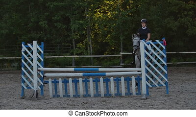 SLOW MOTION, CLOSE UP: Young horsegirl horseback riding...