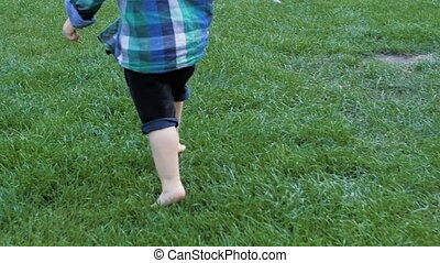 Slow motion closeup footage of adorable toddler boy feet running on fresh green grass at park