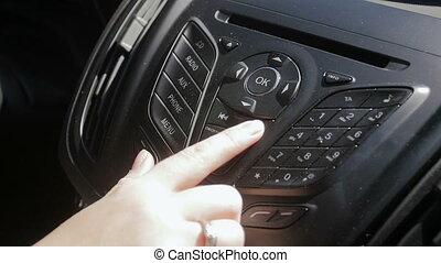 Slow motion closeup footage of female hand adjusting radio...